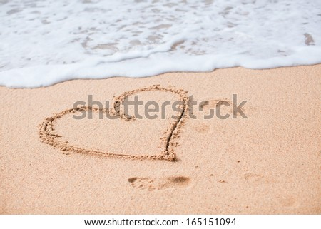 Heart painted in the sand on a tropical beach