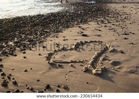 Heart painted on the beach in the sand in the background the sea - stock photo