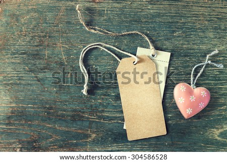 Heart pink color with paper tag on wooden background, vintage effect - retro style - stock photo