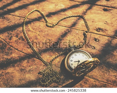 heart pocket watch on a wood background with natural light, photo filter effect. - stock photo
