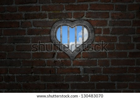 heart prison window in old brick wall - stock photo