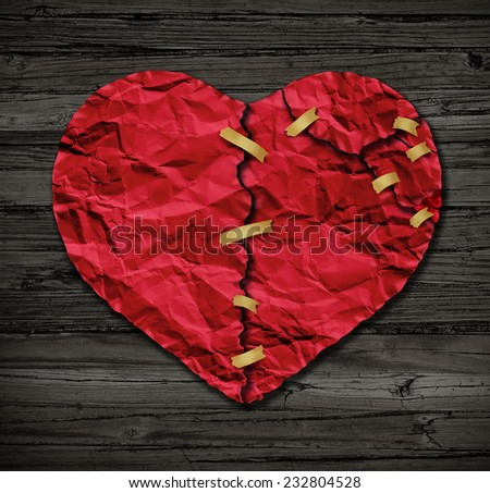 Heart repairing therapy as a red crumpled paper shaped as a torn love icon that has been taped together as a metaphor for therapy on old wood also a symbol of medical cardiovascular health . - stock photo