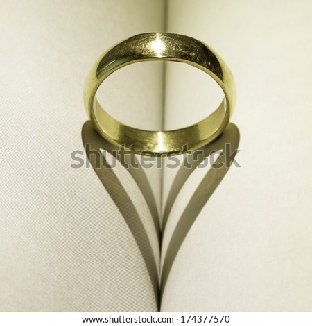 heart shadow with rings on a book middle  - stock photo