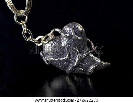 Heart Shape as Trinket for the keys, close up isolated on black background - stock photo