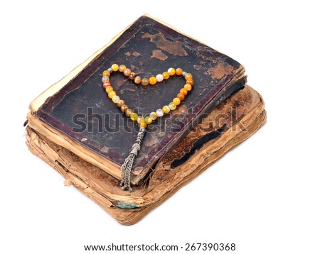 Heart shape beads on old book, on a white background - stock photo