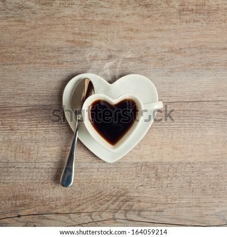Heart shape coffee cup on wooden table - stock photo