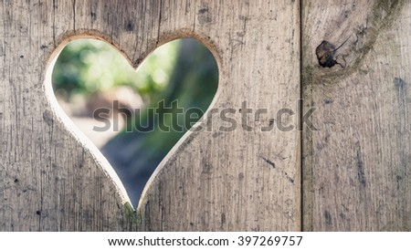 Heart shape cut into wooden boards background with sunshine