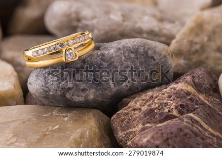 Heart shape diamond ring on blown old stones - stock photo