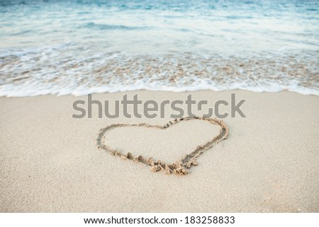 Heart shape drawn in sand on beach