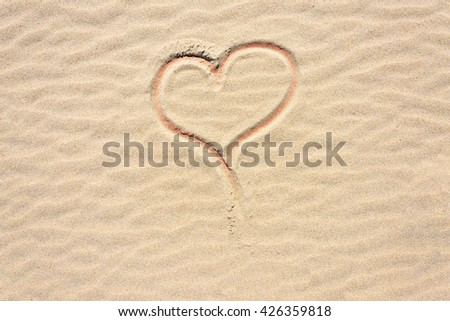 Heart shape drawn into dry sand