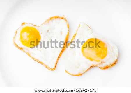 Heart shape fried eggs on the white plate