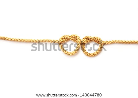 Heart shape from gold rope on white background