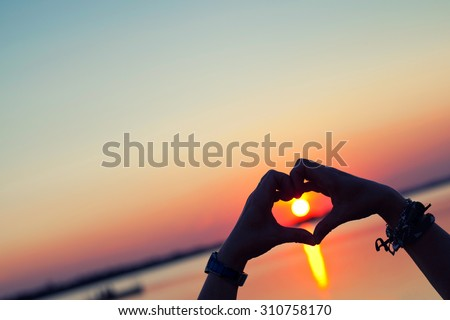 heart shape hand silhouette with sunset