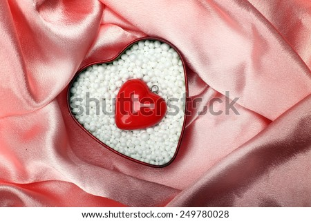 heart shape in polystyrene balls over silk - stock photo