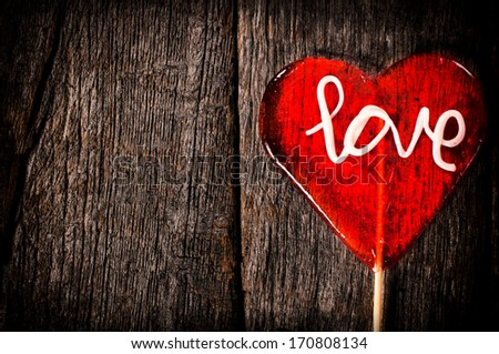 Heart shape lolly pop on the wooden background with empty space - stock photo