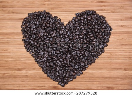 Heart shape made by coffee beans on the wooden background - stock photo