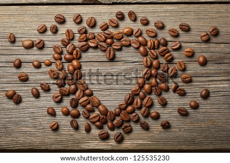 Heart shape made from coffee beans on wooden surface. - stock photo