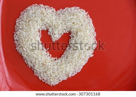 Heart shape made from long grain rice or basmati. Isolated on red background,with copy space. Symbol of love or LUV. White rice or biriyani rice Kerala India - stock photo