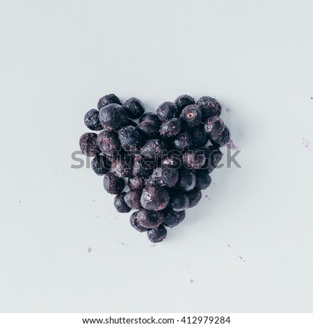 Heart shape made of frozen blueberries on white background. Love concept. Flat lay - stock photo