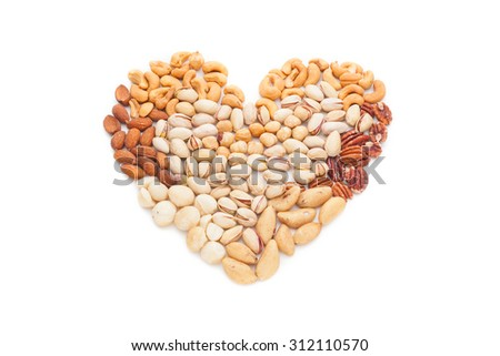 Heart shape made of mixed nuts isolated on white background - stock photo