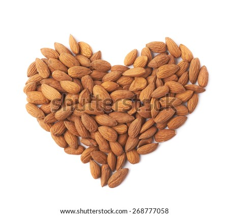 Heart shape made of multiple almond seeds isolated over the white background - stock photo
