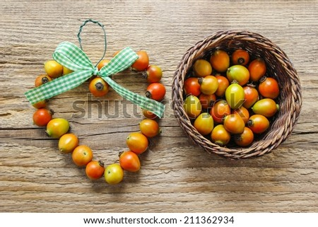 Heart shape made of rose hip fruits on wooden background - stock photo