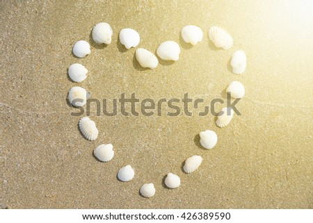 Heart Shape made of shells on the sandy beach with the sunshine touched