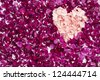 Heart shape made out of carnation petals against pink rose petals - stock photo