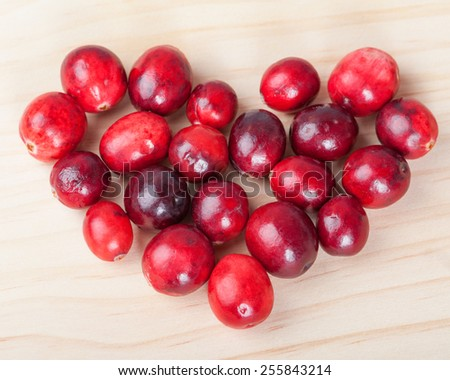Heart shape made with red cranberries on wooden background - stock photo