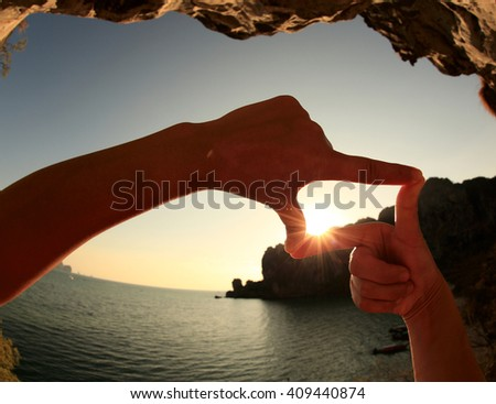 Heart shape making of hands against bright seaside sunset - stock photo