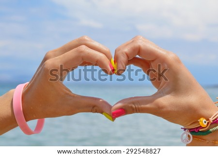Heart shape making of hands against sea and sky looking at water