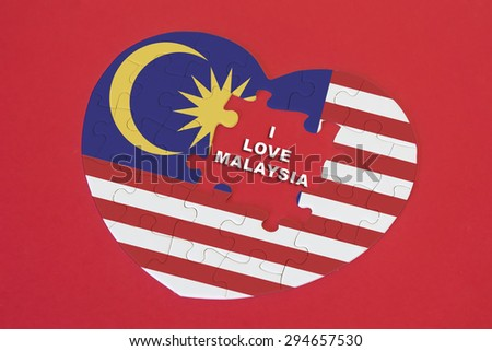 Heart shape Malaysia Flag jigsaw puzzle with a written word I Love Malaysia with red background