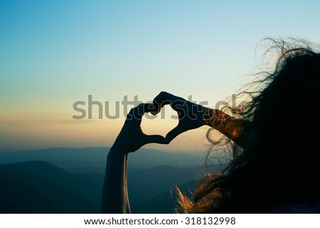 Heart shape. Mountain tourism. Symbol of love. Manifestation of love. Expression of feelings. Enjoy. Girl on a background of mountains. Love and feelings. Long red hair. Wind blowing through her hair. - stock photo