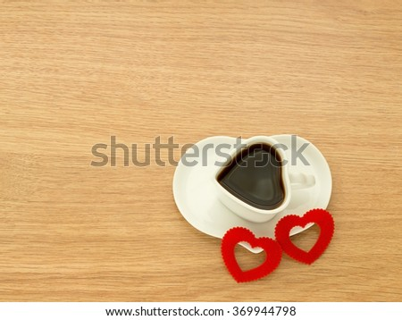Heart shape of cup with coffee and heart shape of plate with two red hearts. Love coffee. Top view. Happy Valentines Day background. - stock photo