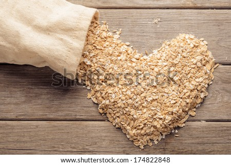 Heart shape of oatmeal flakes near a sack on a wooden table - stock photo