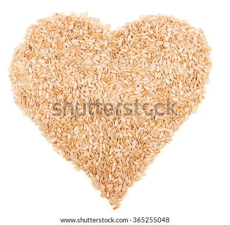 Heart shape of peeled sunflower seeds. Isolated on a white background.