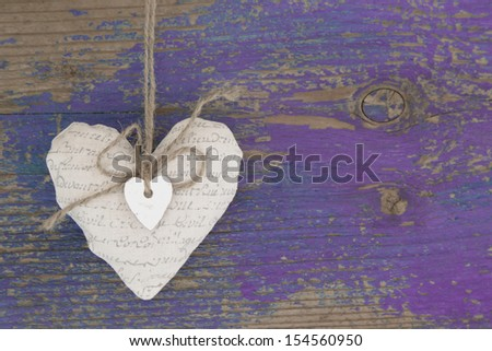 Heart shape on purple wooden surface - to say thank you for a greeting card - stock photo