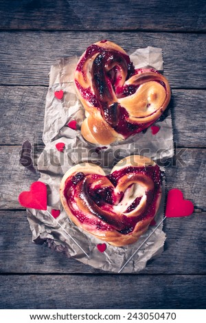 Heart shape pastries stuffed with cherry jelly on wooden background - stock photo