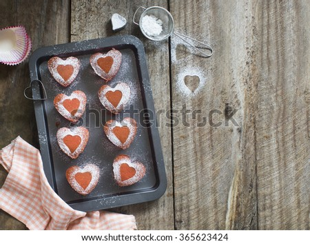 Heart shape pink strawberry cupcake fresh from oven on rustic wooden kitchen table top. Text space image. - stock photo