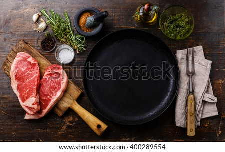 Heart shape Raw fresh meat Steak Striploin for two with ingredients around frying pan - stock photo