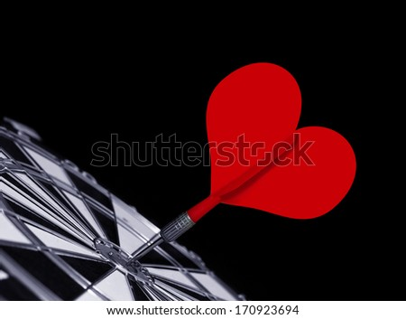 Heart shape red dart  in the center of a target isolated on black - stock photo