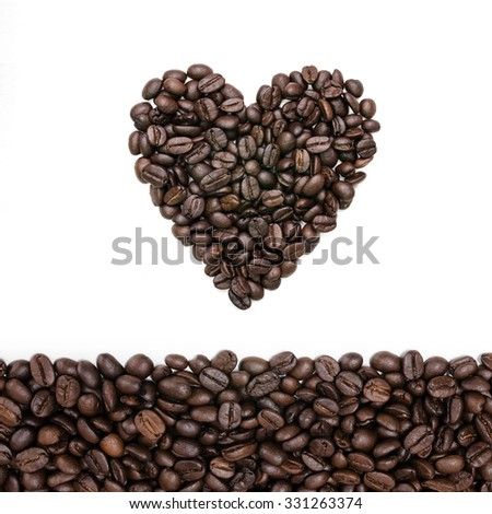 Heart shape roasted coffee beans with coffee beans background isolated on white. - stock photo