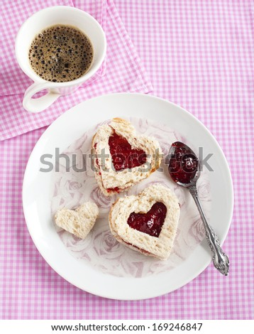 Heart shape sandwich with strawberry jam on a plate