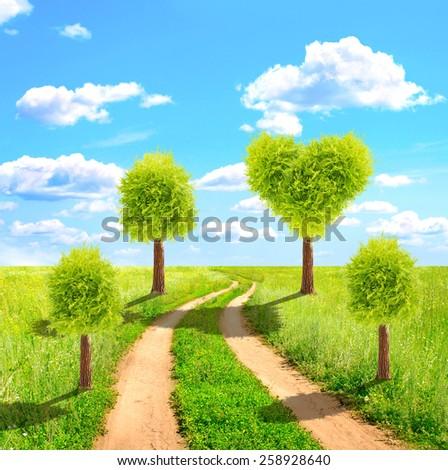 Heart shape tree on green field - stock photo