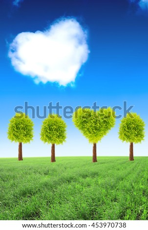 Heart shape tree on green field and one cloud on blue sky background
