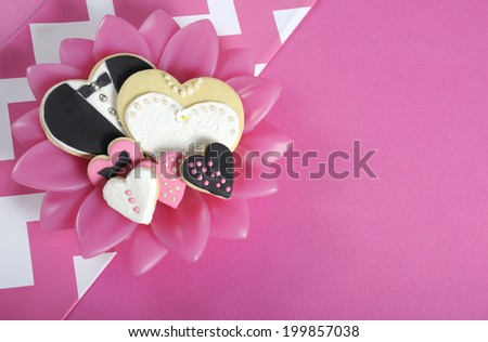 Heart shape wedding bride and groom cookies on modern sixties mod style pink and white chevron stripe table, with copy space.. - stock photo