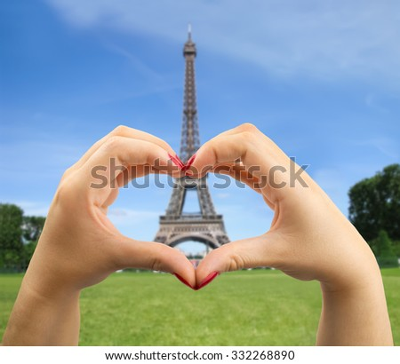 heart shape with hand with Eiffel tower on the background in Paris France - stock photo