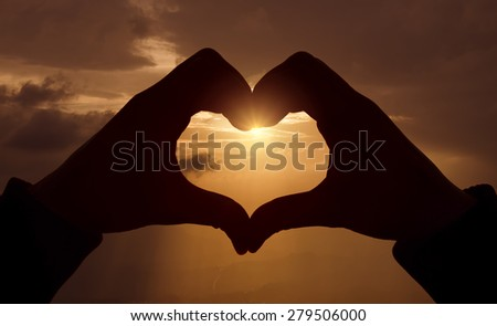 heart shape with hands  on sunset  - stock photo