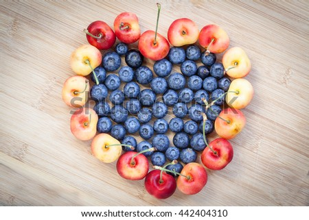 Heart shaped blueberries and cherries on wooden background. Tasty blueberries are antioxidant organic superfood.  - stock photo