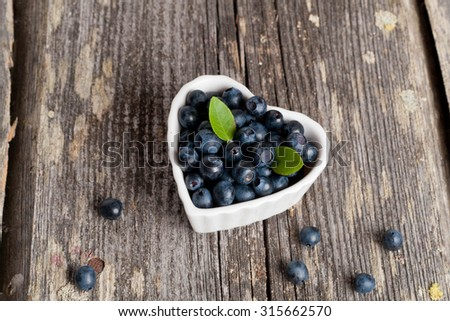 Heart shaped bowl of blueberries on wooden table, horizontal - stock photo